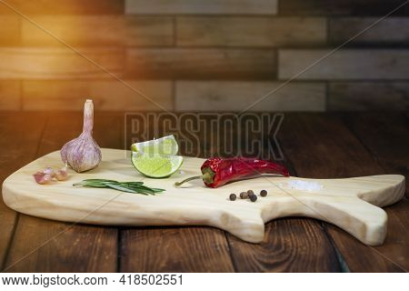 Cutting Board On A Wooden Table With Spices. Handmade Chopping Board. Fresh Vegetables And Cutting B