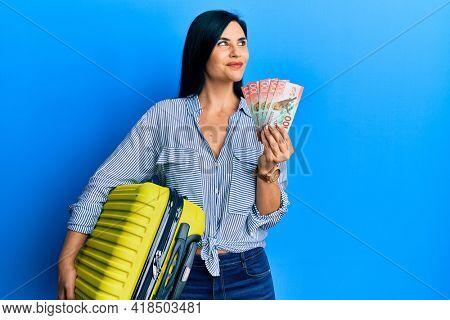 Young caucasian woman holding cabin bag and new zealand dollars banknotes smiling looking to the side and staring away thinking.