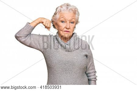Senior grey-haired woman wearing casual winter sweater strong person showing arm muscle, confident and proud of power