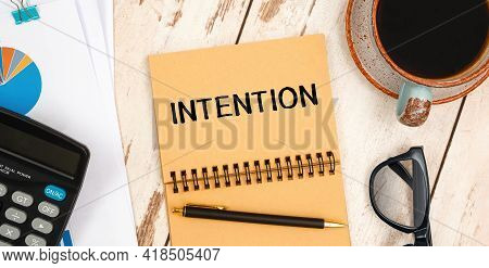 Notebook With Text Intention On The Office Table, Documents, Calculator, Glasses And Pen