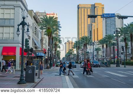 New Orleans, La - October 31: Pedestrians Cross Canal Street With Downtown Buildings In Background O