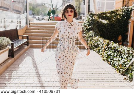 Cheerful Girl In Vintage White Dress Walking Down The Street In Spring Day. Spectacular European Wom