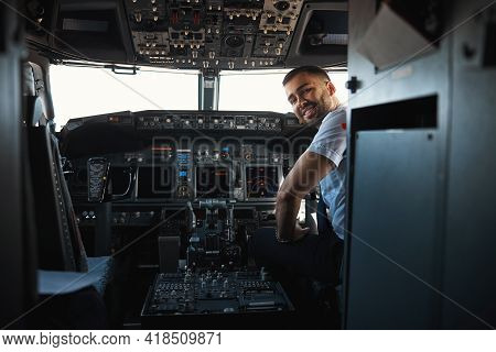 Mirthful Experienced Pilot Looking Happy At His Workplace