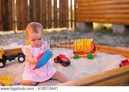 Adorable Baby Play With Sand In Sandbox On Playground