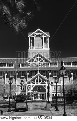 Entrance To Four-story Building Covered With Siding With Turret And Arches Against Clear Sky