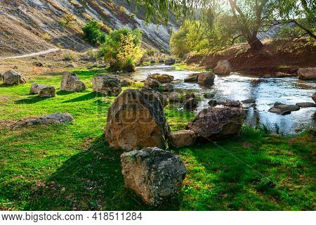 Beautiful Nature With Rocks On The Shore . Idyllic River Valley With Big Stones . Flowing Water Scen