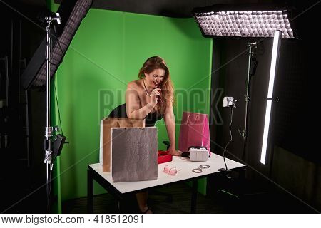 Naughty Female Among Bags Biting A Temple Of Her Glasses
