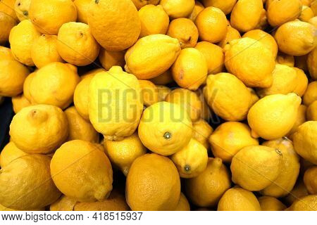 Still life with crop of many ripe lemons fruits as background top view close-up