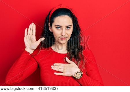 Young hispanic woman wearing casual clothes swearing with hand on chest and open palm, making a loyalty promise oath