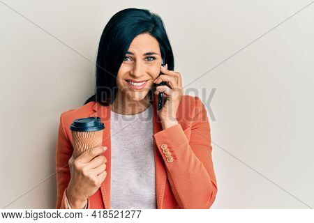 Young caucasian woman having conversation talking on the smartphone holding take away coffee smiling and laughing hard out loud because funny crazy joke.