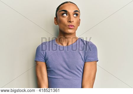 Hispanic man wearing make up and long hair wearing casual t shirt smiling looking to the side and staring away thinking.