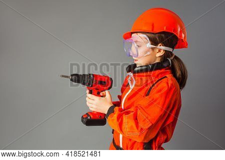 The Little Girl Dressed In A Red Engineering Uniform Is Holding A Screwdriver