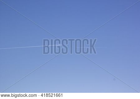 Two Planes Fly Towards Each Other. Inversion Trail Of Clouds From The Plane Against The Blue Sky. Ai