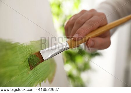 Young Man Painting On Easel With Brush In Artist Studio, Closeup