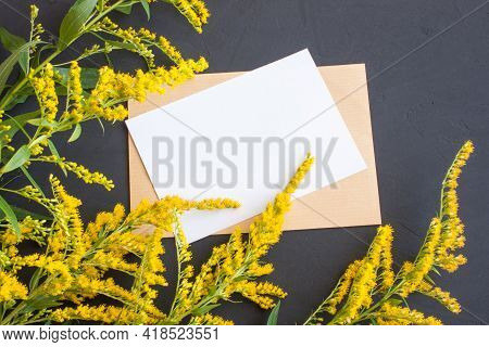 Minimalistic Card Mockup With Goldenrod Twigs, Delicate Yellow Flowers, Kraft Envelope, Top View