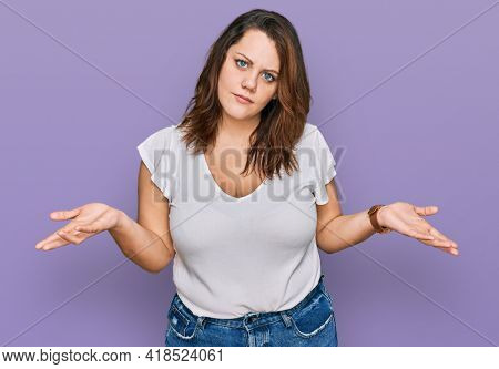 Young plus size woman wearing casual white t shirt clueless and confused with open arms, no idea concept.