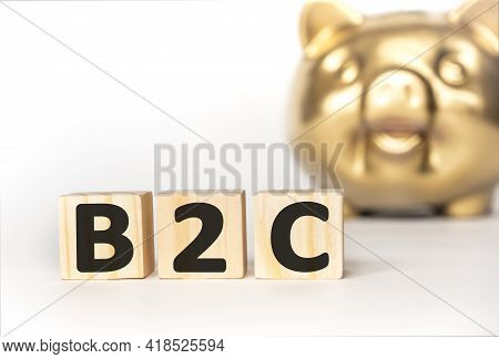 Text B2C On Wooden Cube Blocks. Background Happy Smiling Gold Piggy Bank On Table. Financial Goal, B