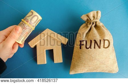 Money Bag With The Word Fund, Wooden House And Euro Bills In Hand. Real Estate Investment Concept. P