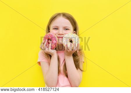 World Donut Day Or No Diet Day. A Little Girl Holding Donuts And Smiling, Holding On A Yellow Backgr