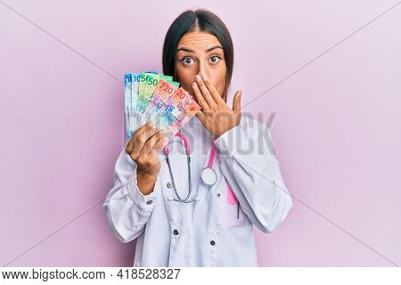 Beautiful hispanic woman wearing medical uniform holding swiss franc banknotes covering mouth with hand, shocked and afraid for mistake. surprised expression