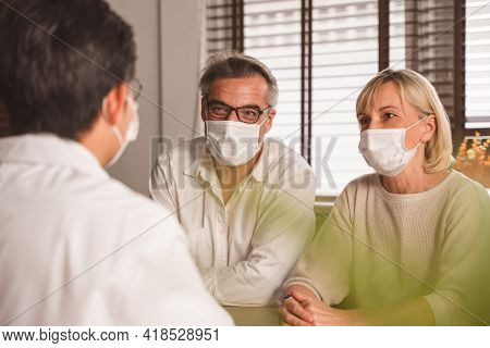Elderly Couple Wearing Protected Face Mask While Listening Or Discussing  With A Man At The Table Wi