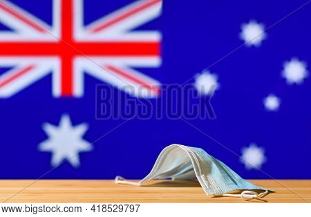 A Medical Mask Lies On The Table Against The Background Of The Flag Of Australia. The Concept Of A M