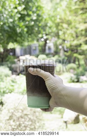 Female Hand Holding Iced Coffee Drink In Disposable Take Away Cup, Stock Photo