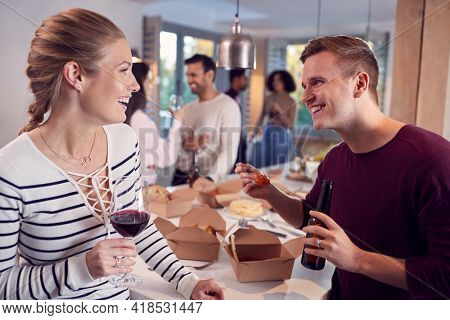 Group Of Multi Cultural Friends Enjoying Drinks Party With Takeaway Food At Home Together