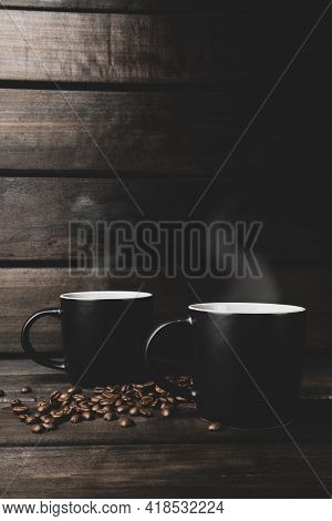 Two Cups Of Hot Coffee With Steam And Coffee Beans On A Wooden And Black Background. Hot Drink. Stea