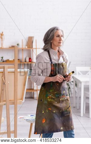 Pleased Middle Aged Artist In Apron With Spills Holding Paintbrush At Home.