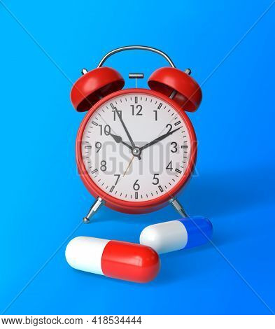 Red And Blue Pharmaceutical Medicine Pills, Tablets, Capsules And Red Alarm Clock On Blue Background