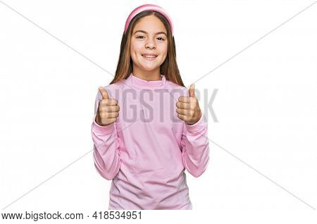 Beautiful brunette little girl wearing casual turtleneck sweater success sign doing positive gesture with hand, thumbs up smiling and happy. cheerful expression and winner gesture.