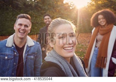 Portrait Of Multi Cultural Group Of Friends Enjoying Outdoor Walk In Fall Or Winter Countryside