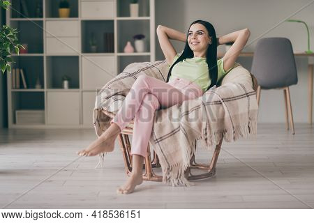 Portrait Of Lovely Cheerful Long-haired Girl Sitting In Cosy Chair On Checkered Cover Enjoying Rest