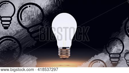 Composition of lit light bulb over light bulb icons on black background. lightbulb moment, electricity, inventions and technology concept digitally generated image.