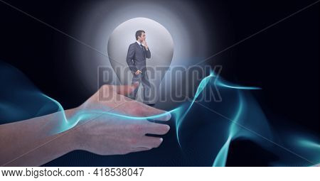 Composition of hand over businessman thinking inside light bulb over halo on black background. lightbulb moment, electricity, inventions and technology concept digitally generated image.