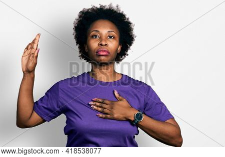 African american woman with afro hair wearing casual purple t shirt swearing with hand on chest and open palm, making a loyalty promise oath