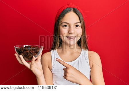 Beautiful brunette little girl holding bowl of raisins smiling happy pointing with hand and finger