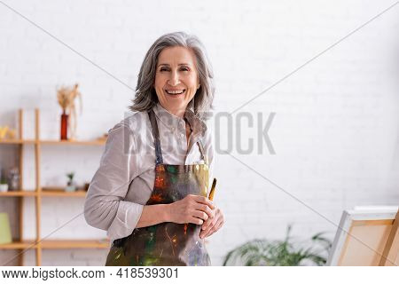 Cheerful Middle Aged Artist In Apron With Spills Holding Paintbrush Near Easel.