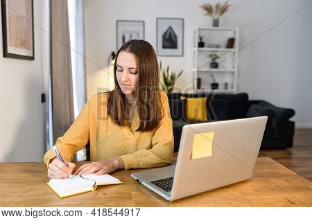 Online Training. Female Student Watching A Lecture, Webinar Using A Laptop, Sits At The Table And Wr