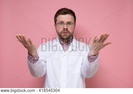 Young Bearded Doctor In Round Glasses And A White Coat Is In Perplexity, He Throws Hands Up And Look