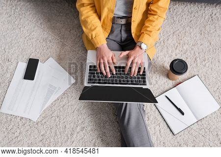 Partial View Of Freelancer Sitting On Floor And Typing On Laptop Near Mobile Phone And Coffee To Go.