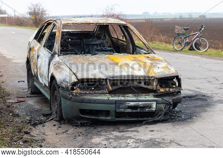 Burned Car After An Accident On The Asphalt Road. Front View. Arson Of A Car, Criminal Showdowns