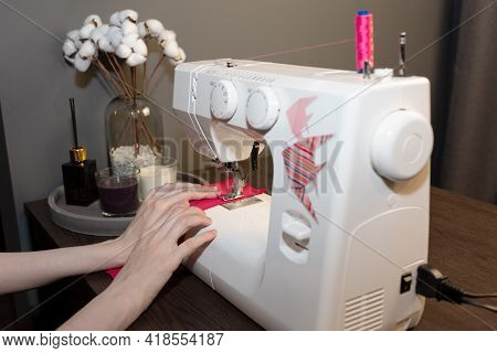 A Woman Is Sewing With An Electric Sewing Machine. Tailors Workshop. Cotton Bouquet, Scented Candles