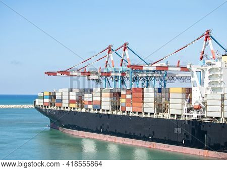 Container Ship Docked At The Port Of Ashdod, Israel.  Gantry Crane Working To Load Unload Freighter
