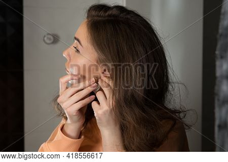 Close Up Of Beautiful Woman Puts On Heart Shaped Earrings