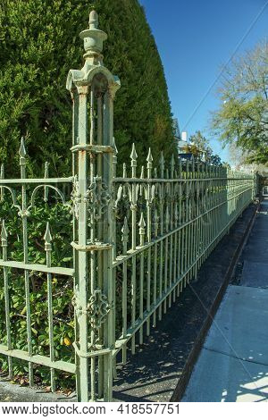 A Green Wrought Iron Fence Fading In The Distance