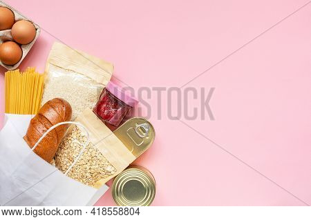 Donation Food On Pink Background With Copy Space. Flat Lay. Top View, Mock Up. Rice, Canned Food, Oa