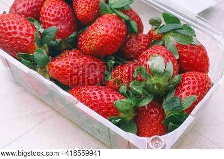 Freshly Harvested Strawberries In A Plastic Container. Close Up.