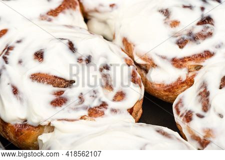 Close-up Of Sweet Cinnabon Bun Covered With Sugar Glaze. Homemade Buns.